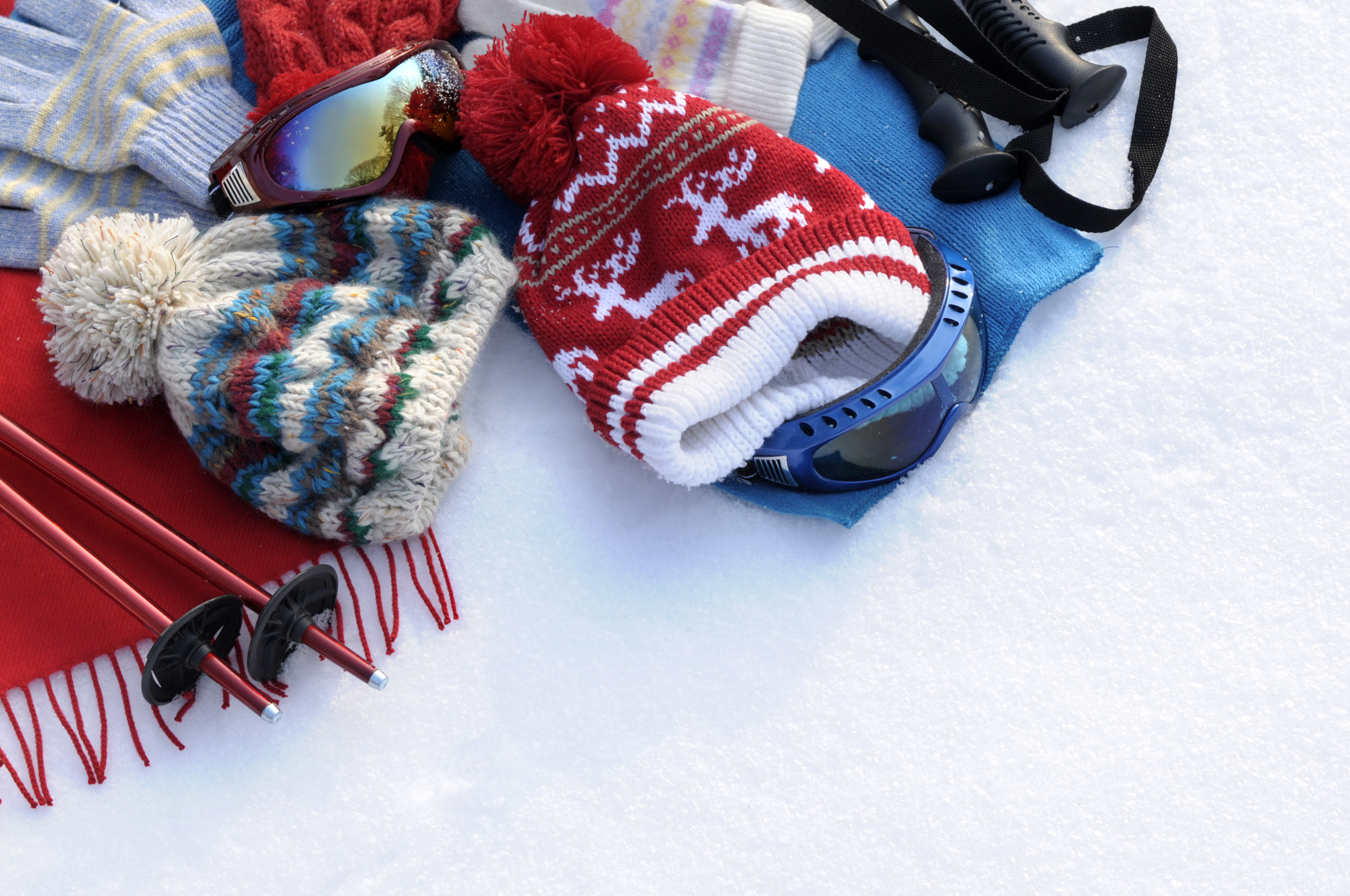 Winter sports background with ski poles, goggles, hats and gloves with copyspace (picture taken in fresh snow with directional winter sun).